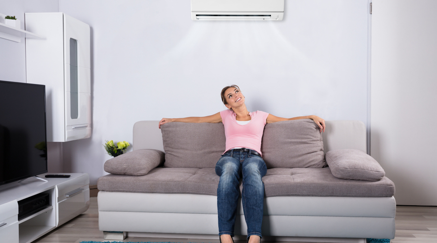 a woman sitting under an ac in a room without windows