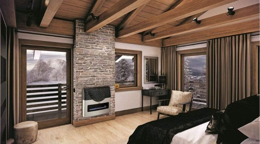 a modern bedroom with the best indoor ventless propane heater installed in a wall