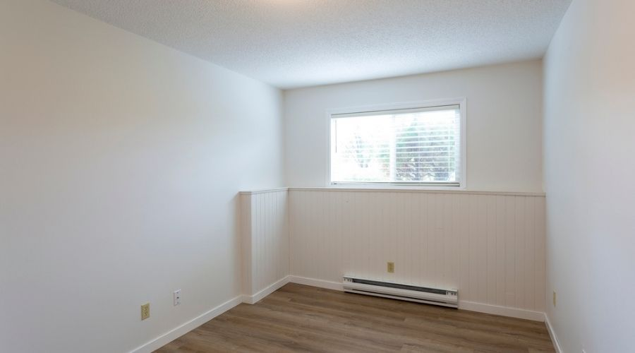 Interior of empty renovated apartment condo rental unit with baseboard heater